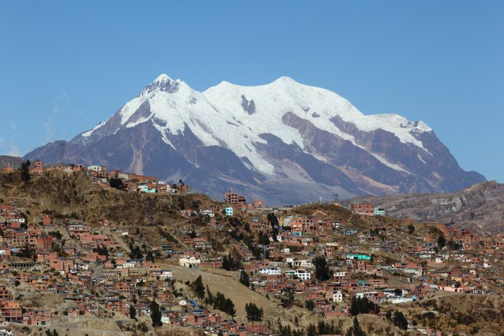 La Paz continues to grow up hillside on outskirts , Mt Illimani in background , Bolivia